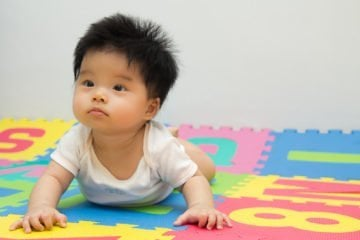 Portrait of a little baby girl crawling on floor